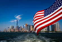 Lower Manhattan View From Cruise Ship Or Yacht With The Flag Of The United States Of America In New York. Scenic View To NY Downtown And City Centre. Staten Island Ferry.