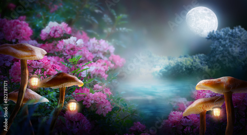 Fototapeta premium Fantasy mushrooms with lanterns in magical enchanted fairy tale landscape with forest lake, fabulous fairytale blooming pink rose flower garden on mysterious background, glowing moon ray in dark night