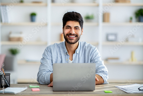 Fotografija Positive arab male employee smiling at camera while working on laptop at home of