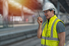 Worker Using Radio Communication  While Stand On Site Construction Of Train Station On Background.