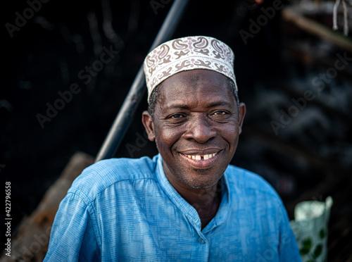 Obraz na plátně Senior man sitting on coast smiling nice with hat , High quality photo