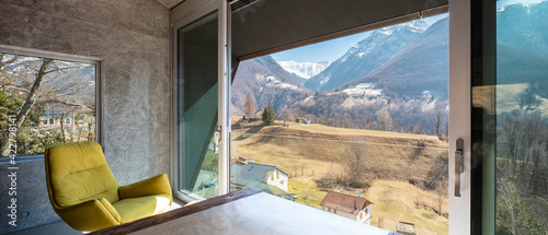 Interior of a beautiful modern house, where you see a table, a yellow armchair a Fototapeta