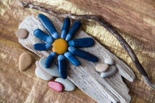 Handicraft Made Of Stones, Paints And Wood: A Flower With Blue Petals On A Wooden Stand.