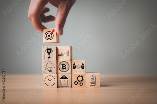 Fototapeta Hand stack woods block has an icon on it Goals , Planning, Success, Rewards, Communication target, Teamwork for business development, project management, corporate strategy development. obraz
