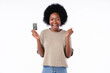 Extremely happy young african girl holding credit card isolated in white