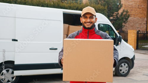Young indian man delivering parcel. Giving cardboard box. High quality photo