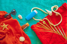 Beach Concept Summer Vacation Lilac Turquoise Towel With A Red Bag With Shells Sunscreen And Sunglasses