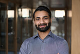 Portrait of young happy indian business man executive looking at camera. Eastern male professional teacher, smiling ethnic bearded entrepreneur or manager posing in office, close up face headshot.