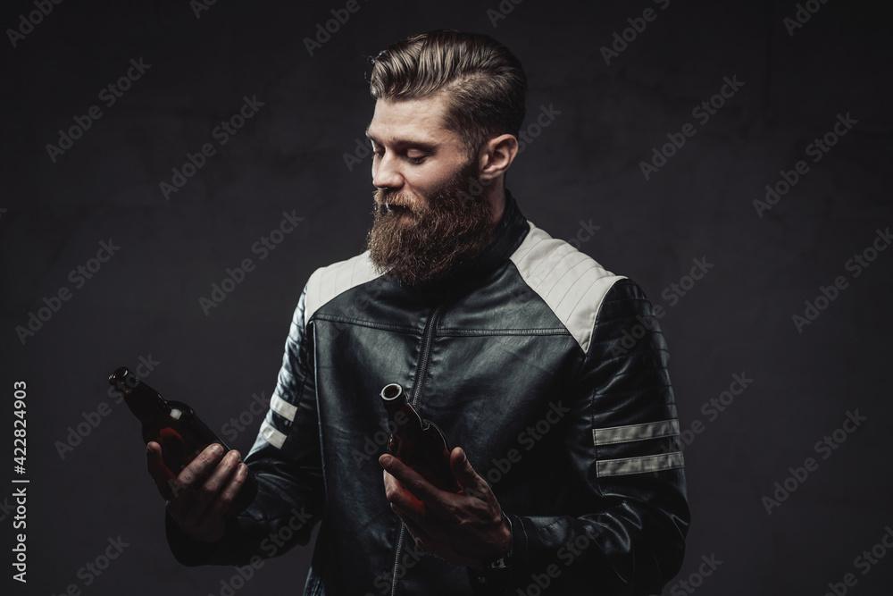 Fototapeta Bearded guy posing with bottles in dark background - obraz na płótnie