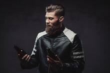 Bearded Guy Posing With Bottles In Dark Background