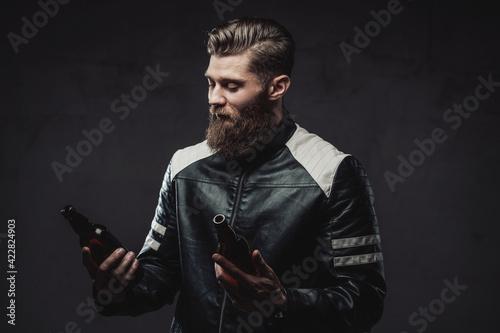 Fototapeta Bearded guy posing with bottles in dark background obraz na płótnie