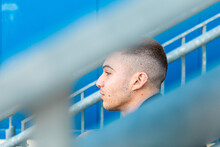 Face Portrait Of A Handsome Young And Rocker Man Sitting On Stairs In The Street With Blue Background