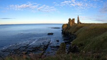 4k Real Time Clip Of Castle Sinclair Girnigoe Near Wick, Caithness, Scotland At Sunset. Showing Castle, Cliffs, Sea, Waves On Rocks. Blue Sky And Clouds With Orange On Horizon. No People. On NC500.