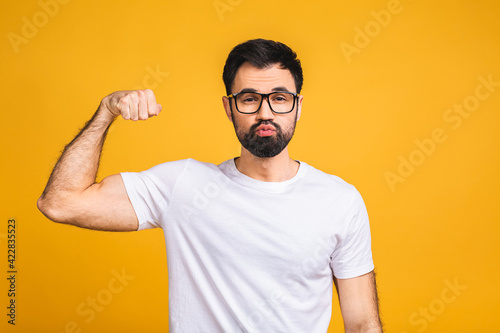 Billede på lærred Portrait of a happy young bearded man dressed in t-shirt showing biceps isolated over yellow background