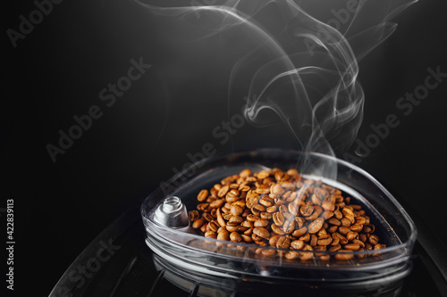 fresh roasted coffee beans with smoke in coffeemaker bean container, close-up vi Fototapet