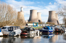 Small River Boat Moored Near A Power Station