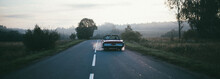A Retro Car Drives Along The Road At Dawn. The Convertible Drives Off Into The Distance On A Deserted Road