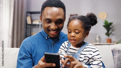 Close up of joyful cute african american little girl child sitting with father on couch in living room and tapping on smartphone. Happy dad teaching small kid daughter using cellphone at home