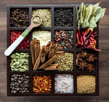 Top Down View Of A Variety Of Whole Spices In A Compartment Box With A Wooden Spoon Of Fennel Seeds On Top.
