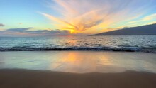 Wide Shot Of Hawaii Beach At Sunset With Waves Rolling To Wet Sandy Beach