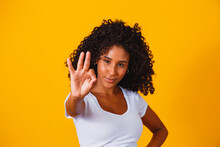 Beautiful Curly-haired Girl Using Her Hands Ok Sign. Yellow Background. Afro Woman Ok