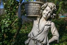 Photo Of A Boy Wearing A Basket, A Concrete Statue
