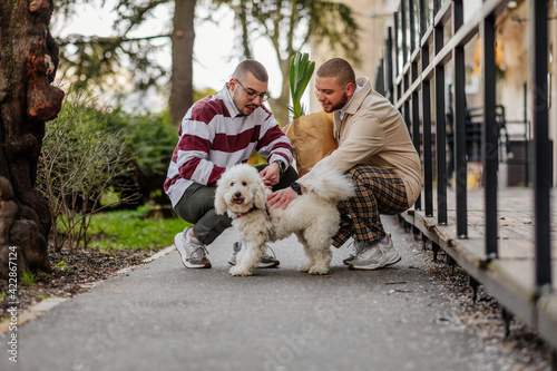 Gay male couple cuddling adorable dog in front of store where they were in shopp Fototapeta