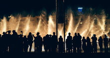 Singing And Dancing Fountains In Dubai With Silhouettes Of Crowd Of Tourists Watching Show And Taking Photos, Horizontal Panoramic Image.