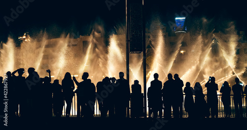Canvastavla Singing and dancing fountains in Dubai with silhouettes of crowd of tourists watching show and taking photos, horizontal panoramic image