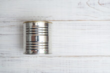 Closed Metal Can Of Canned Food On A White Wooden Background.