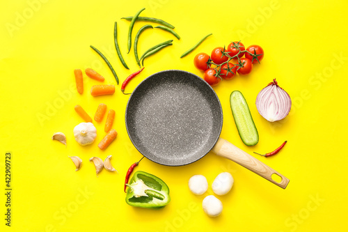 Obraz Frying pan and different vegetables on color background - fototapety do salonu