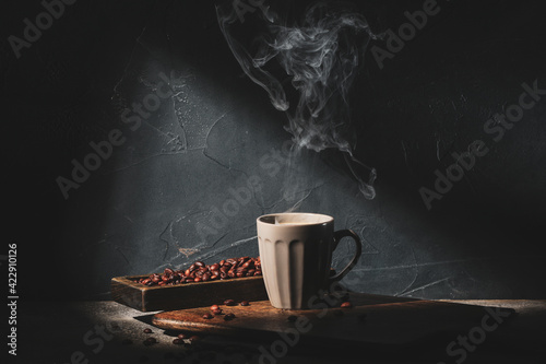 Fototapeta Cup of hot coffee and beans on dark background obraz