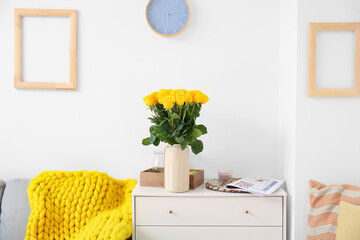 Vase with beautiful yellow roses on chest of drawers in interior of room