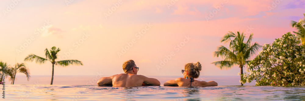 Fototapeta Panoramic photo of couple in pool enjoying tropical vacation by sunset