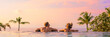 Panoramic photo of couple in pool enjoying tropical vacation by sunset