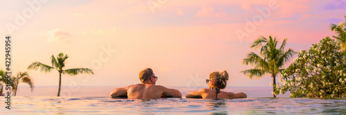 Obraz Panoramic photo of couple in pool enjoying tropical vacation by sunset - fototapety do salonu