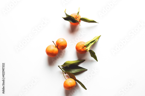 Fototapeta Oranges fruits composition with green leaves and slice on white wooden background, top view obraz