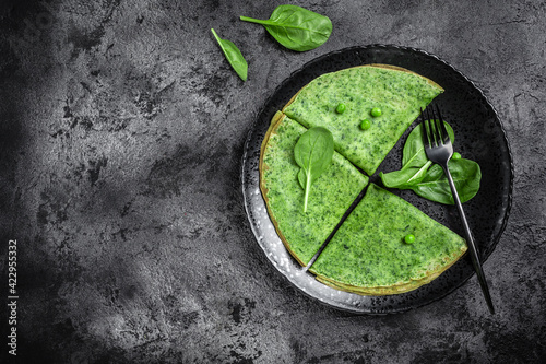 Photo Green vegan crepes with spinach on dark background