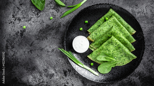 Fototapeta Spinach green pancakes crepes with sour cream. Long banner format, top view obraz