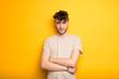canvas print picture - Junger Mann im T-Shirt vor einem gelben Hintergrund