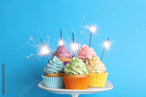 Birthday cupcakes with burning sparklers on stand against light blue background