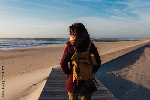 Fotografia backpacker young caucasian woman relaxing at the beach at sunset