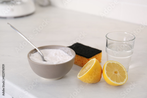 Baking soda, lemon, vinegar and sponge on counter. Natural detergent
