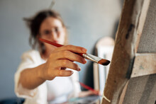 Female Artist Painting On Canvas With A Paintbrush In The Art Studio. A Woman Painter With Glasses Painting In Her Workshop.
