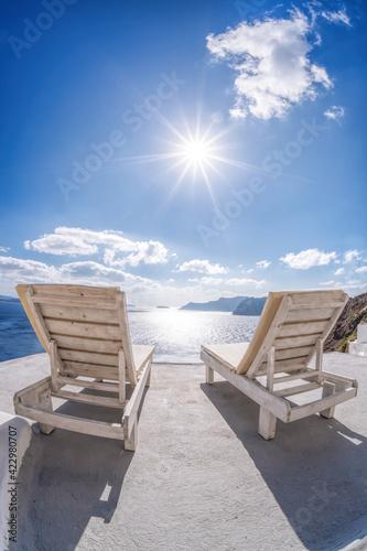 Tela Relaxation on sunbeds against sunset in Oia village, Santorini island, Greece