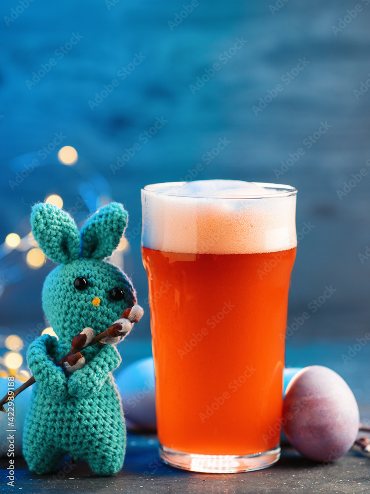 Handmade knitted bunny toy, glass of craft seasonal beer, Happy Easter concept - obrazy, fototapety, plakaty