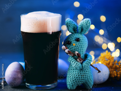 Fototapeta A glass of dark craft beer, Easter colored eggs, handmade knitted bunny with willow branch, celebrate Easter concept obraz na płótnie