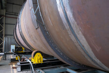 Production Line, Unfinished Pipe With Not Welded Seam Moving On Roller Conveyor.