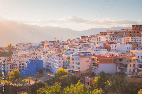 Fototapeta Cityscape view of the hilltop village and old town medina of Chefchaouen, Morocco with beautiful golden sunset or sunrise light
