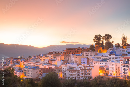 Obraz na plátně Colourful, vibrant sunset or sunrise cityscape view of the illuminated hilltop village and old town medina of Chefchaouen, Morocco